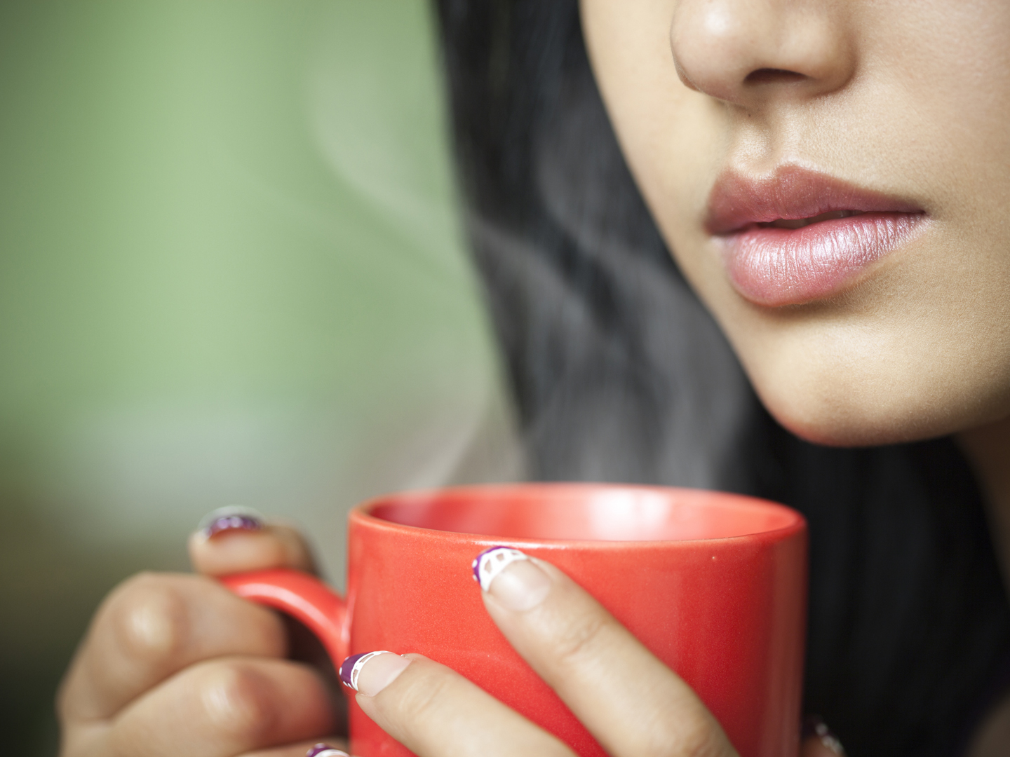 Indoor cropped close-up image of a beautiful Asian young woman holding a hot steaming coffee mug. One person, horizontal composition with selective focus and copy space.