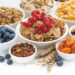 assortment of different breakfast cereal, dried fruit and fresh berries on white wooden table, closeup, horizontal