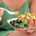 Poke bowl salad plate. A traditional local Hawaii food dish with raw marinated ahi yellowfin tuna fish. Woman sitting on beach eating lunch.